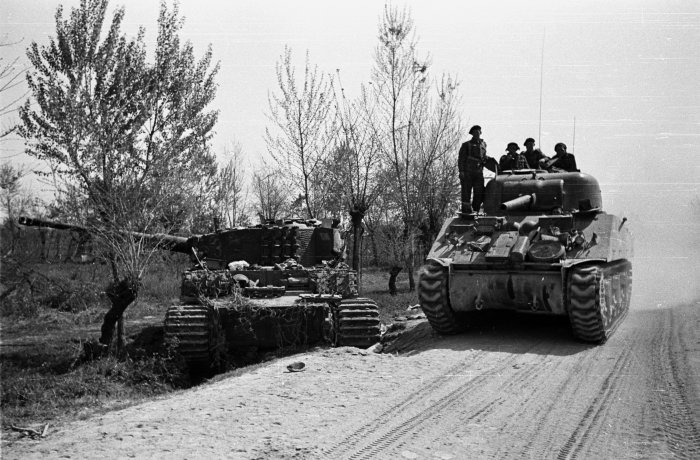 nz tank passing a knocked out german tank across the senio river. 10 april 1945. da09168f-1